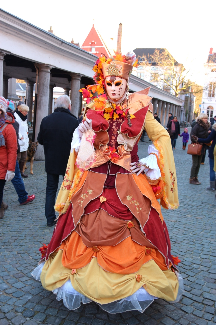 A woman wearing a Venetian costume is dressed like Autumn next to Bruges Fish Market Venetian costumes in Bruges